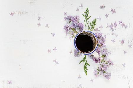 Cup of coffee and purple lilac flowers on the wooden background; flat lay, top view Archivio Fotografico