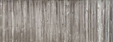 unpainted: Long gray wooden fence consisting of old weathered unpainted boards Stock Photo