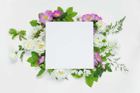 leaves frame: Scrapbook page of wedding or family photo album, frame with wild rose, white flowers and green leaves on light wooden background; top view, flat lay, overhead view