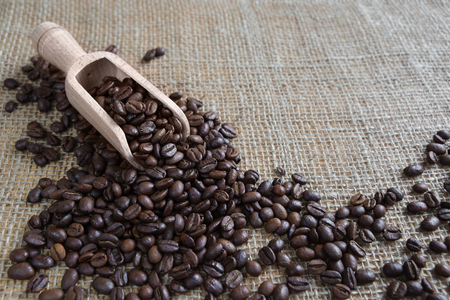 coffee spill: Coffee beans spill out of a wooden scoop on the background of rough burlap