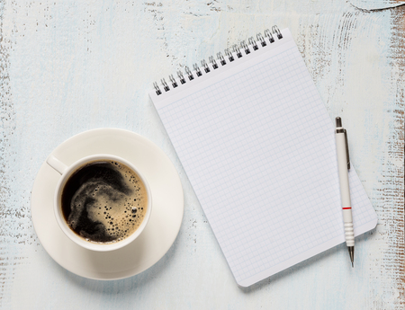 crema: Black coffee with crema in porcelain cup,  checkered notepad and pencil on a light wooden background; top view, flat lay; overhead view
