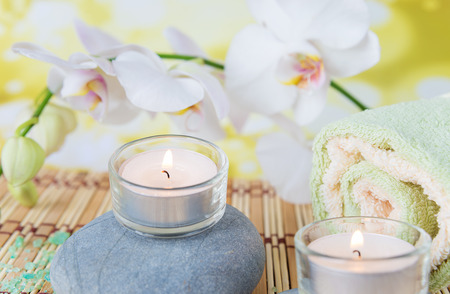 spa flower: Spa concept: bath towels, two lighted candles on a wild rock and a branch of white orchid