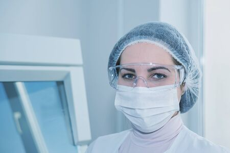 protective: Woman scientist in a white protective clothing preparing for the experiments in the laboratory looking directly