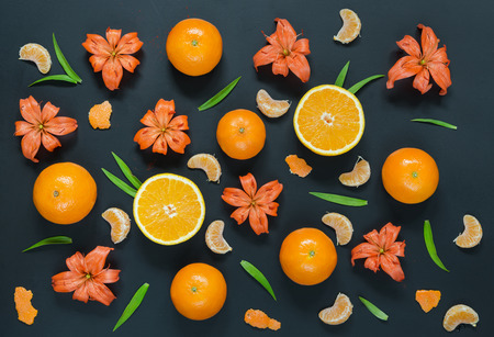 distributed: Pattern with lily flowers, oranges and mandarines on black background. Flat lay, top view