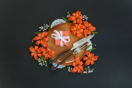 Terracotta plate decorated with orange lilies flowers and gift box tied with white lace ribbon and exclusive forged cutlery on a black table; top view, flat lay