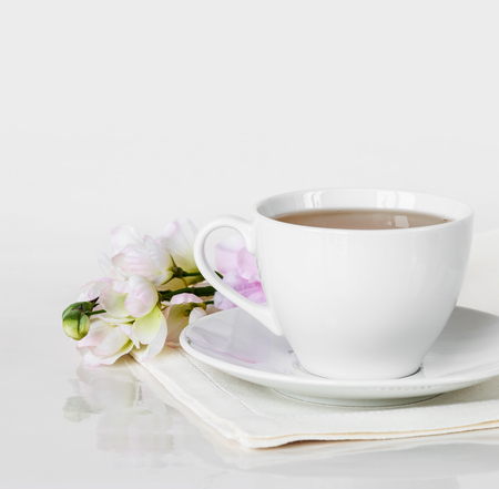 porcelain flower: Hot tea in a white porcelain cup with saucer,linen napkin and flower in the backdrop, on a white background, with space for text