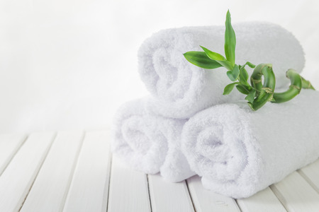 white towels: SPA concept: stack of three rolls of white fluffy bath towels with green Lucky bamboo plant on the background of white boards Stock Photo