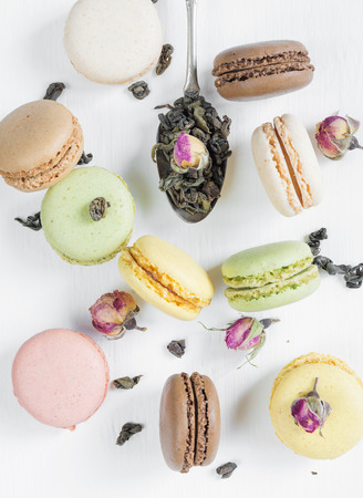 almond bud: Multicoloured macaroons, tea, dried rose buds and teaspoon on white background; top view, flat lay
