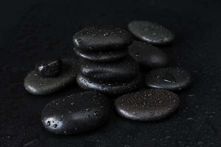 black stones: Spa concept with heap of the black basalt massage stones covered with water drops on a black background Stock Photo