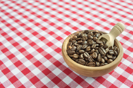 wooden scoop: Coffee beans in the wooden bowl and wooden scoop are on a background of red and white checkered cloth Stock Photo