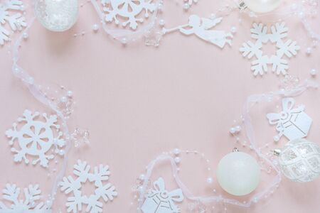 ange: Christmas frame composed of white christmas decoration: snowflakes, balls, flying angel and gift boxes on pink background. Flat lay composition for websites, social media, business owners, magazines,  bloggers, artists etc.