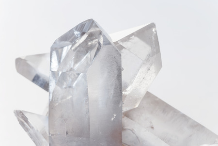 twinning: Cluster of several transparent quartz crystals close-up on a white background