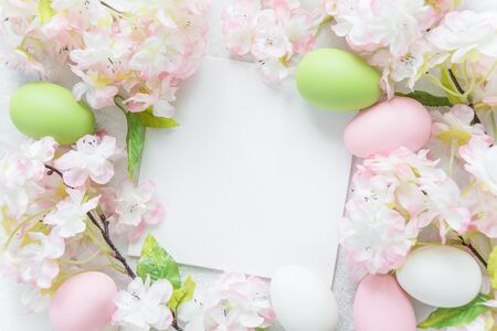 Beautiful delicate Easter frame with pink cherry flowers and multicolored Easter eggs Stock Photo