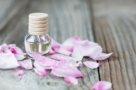 Glass vial with rose essential oil and petals of pink rose on a wooden background