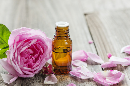 Dark glass vial with rose essential oil and flower of pink rose on a wooden background Archivio Fotografico