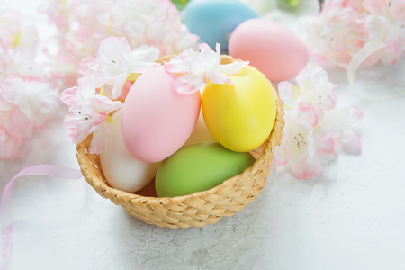 Easter composition with multicolored easter eggs in a wicker basket on the background of delicate pink flowers of the cherry blossoms