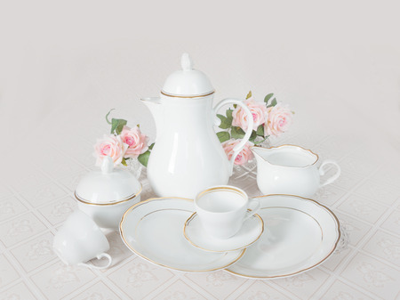 Classic white crockery for tea ore coffee: teapot, coffee pot, cup, serving plate, sugar bowl and creamer on a beautiful tablecloths