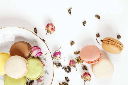 Multicoloured macaroons on beautiful porcelain plate, tea and dried rose buds on white background; top view, flat lay Stock Photo