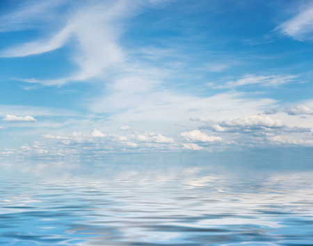 Panorama of vast blue summer sky with fluffy white cumulus and cirrus clouds reflected in a water surface with small waves Stock Photo