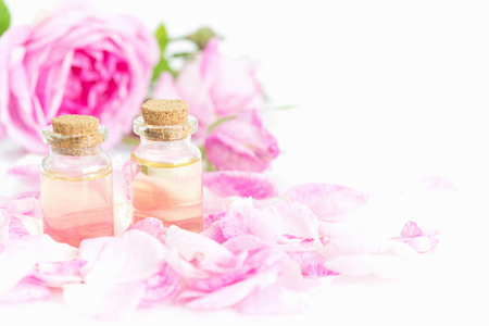 Two vials of rose essential oil, pink roses and rose petals isolated on a white background, with copy-space Фото со стока