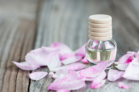 Glass vial with rose essential oil and petals of pink rose on a wooden background, with copy-space Stock Photo
