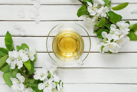 Glass cup of green tea and branches of apple-tree flowers on an old wooden shabby background