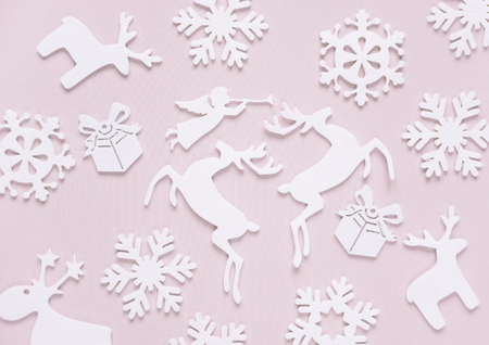 ange: Christmas background composed of white christmas decoration: snowflakes, deers, flying angel and gift boxes on pink background. Christmas wallpaper. Flat lay composition for websites, social media, business owners, magazines,  bloggers, artists etc.