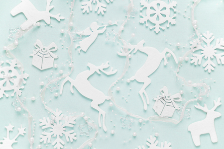 Christmas background composed of white christmas decoration: snowflakes, deers, flying angel and gift boxes on blue background. Christmas wallpaper. Flat lay composition for websites, social media, business owners, magazines,  bloggers, artists etc.