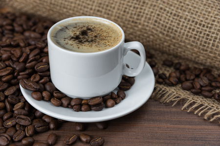 frothy: Cup of black coffee with roasted coffee beans on the dark wooden background with rough burlap