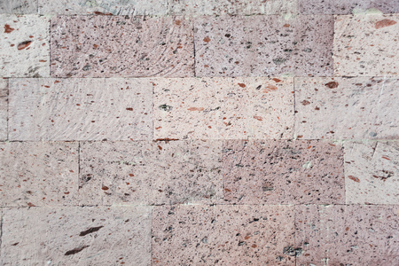 Abstract background: a wall of natural pink tuff