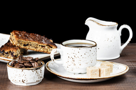 processed grains: Vintage ceramic cup of coffee, coffee beans, cane sugar and a piece of chocolate cake Stock Photo