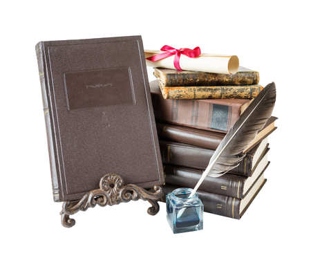 Old hardcover brown books, feather pen in inkpot, bookrest and scroll tied with red bow, isolated on white background