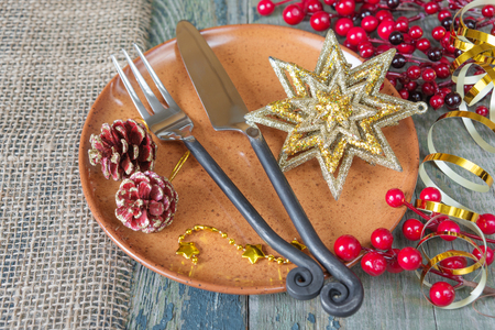 Beautiful Christmas table: handmade still  knife and fork are on the brown ceramic plate, golden star and ribbon, red holly berries which is located on a old wooden boards Фото со стока