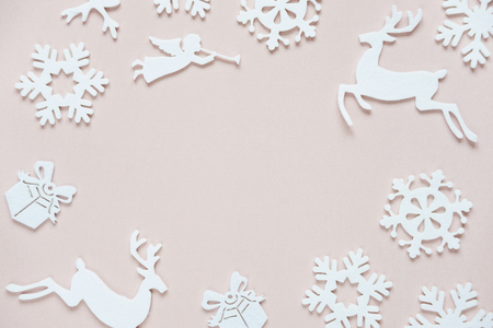 Christmas frame composed of white christmas decoration: snowflakes, deers, flying angel and gift boxes on pink background. Flat lay composition for websites, social media, business owners, magazines,  bloggers, artists etc.