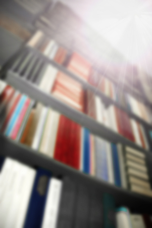 Blurred background: the big book shelfs in library with beams of bright light from the corner Stok Fotoğraf