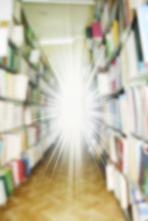Blurred background: the big book racks in library with beams of bright light from the center