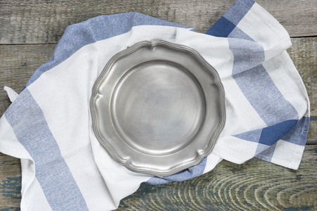 Empty pewter plate and kitchen towel on a rough wooden table, top view