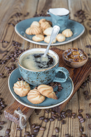 Black coffee in blue ancient cup and biscuit cookies on old dark cutting board