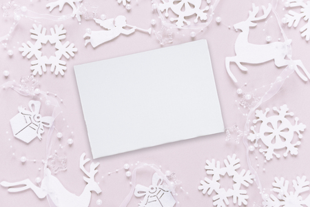 Christmas greeting card composed of white christmas decoration: snowflakes, deers, flying angel and gift boxes on pink background. Flat lay composition for websites, social media, business owners, magazines,  bloggers, artists etc. Banco de Imagens