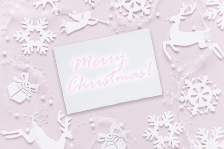 Christmas greeting card composed of white christmas decoration: snowflakes, deers, flying angel and gift boxes on pink background with inscription Merry Christmas! Flat lay composition for websites, social media, business owners, magazines,  bloggers, artists etc.
