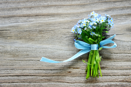 Small bouquet of blue forget-me-not flowers, tied with a blue ribbon, on the background of old wooden plank, with copy-space