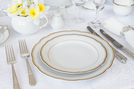 Classic serving for a gala dinner with luxurious porcelain, silverware and spring flowers on a white tablecloth