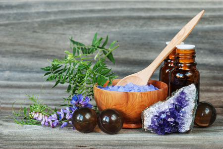 Spa concept. Salt for baths, bottles with essential oils, stone amesist and blue flowers on an old wooden background