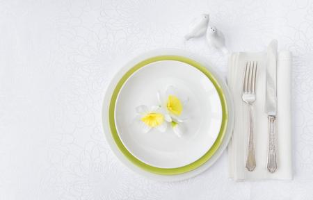 白いテーブルクロスに豪華な磁器、銀器、春の花をまとったガラディナーのクラシックなサービス、コピースペース付き 写真素材 - 99188979
