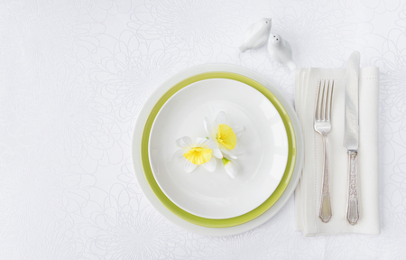 Classic serving for a gala dinner with luxurious porcelain, silverware and spring flowers on a white tablecloth, with copy-space Foto de archivo