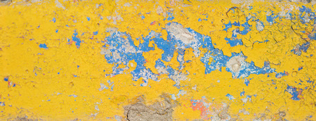 Old cracked wall painted with bright yellow and blue paint. Grunge peeling background