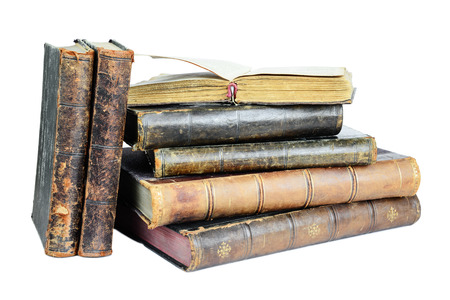 Open book lies on a pile of old books isolated on a white background