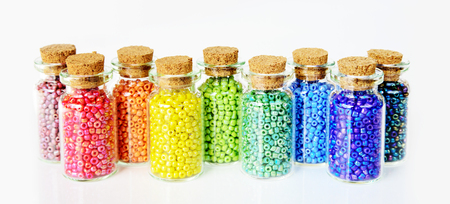 Multicolored beads in small glass jars on a white background Stock Photo