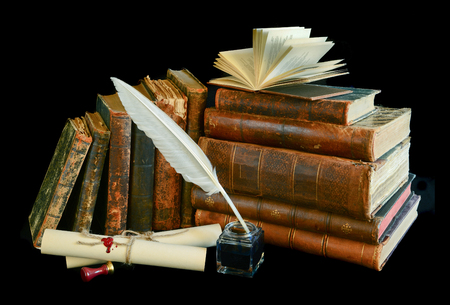 Still life with a letter, a pen and old books isolated on a black background