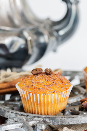 Cupcakes with chocolate shavings surrounded by coffee beans